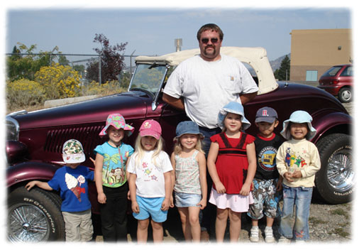 Daycare children with Special visitor Norm who brought in his antique Ford Roadster for everyone to see.