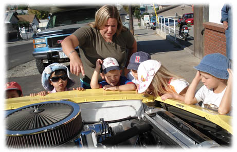 On a field trip to OK Tire to see a race car - children peering in under the hood to learn about the engine.